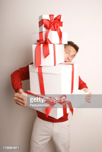 surprised young man holding stack of holiday christmas gifts stock photo