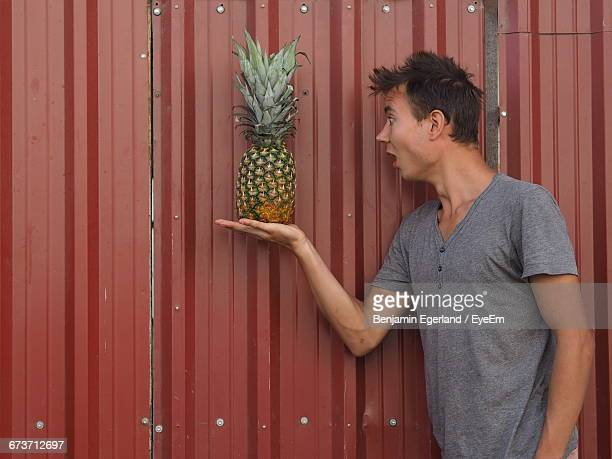 Surprised Young Man Looking At Pineapple On Palm By Metal Sheet