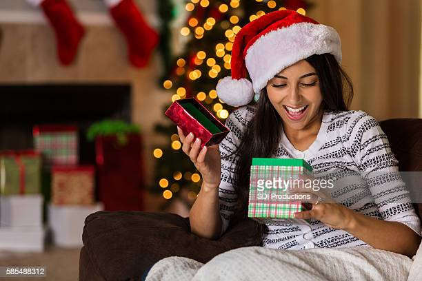 Surprised young woman opens Christmas gift