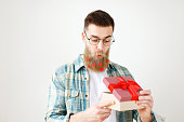 Surprsied handsome man with thick beard and mustache looks with intriguing expression as opens wrapped gift box, being curious what is there, wears round spectacles and checkered shirt, isolated.