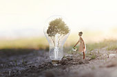 surreal image of a woman watering her plant that needs energy to a light bulb