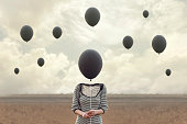 surreal image of woman and blacks balloons flying