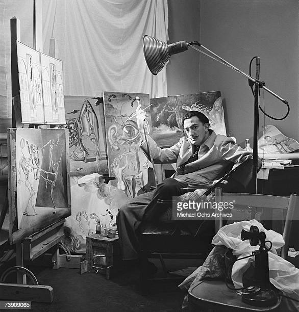 Surrealist artist Salvador Dali poses with his oil paintings at his studio on the 8th floor of the Zeigfeld Theatre in 1943 in New York City New York