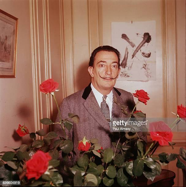 Surrealist Salvador Dali behind a spray of large red roses France ca 1960s