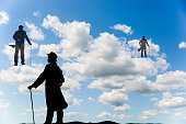 Surrealistic image of silhouettes of men with a cane and bowl hat climbing up the clouds in the sky