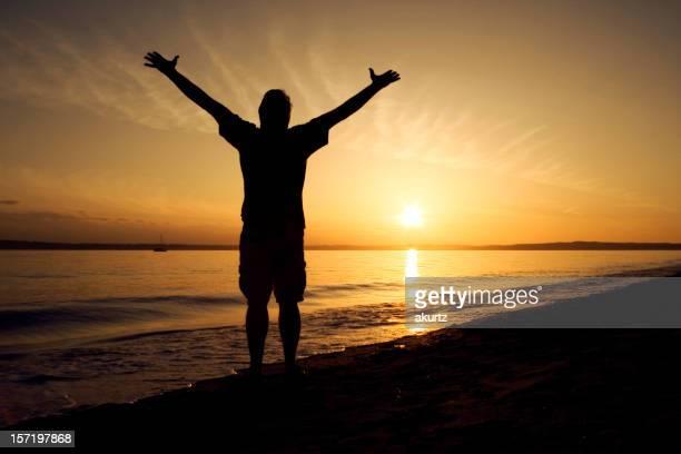 Abandonnez-vous à la plage adulte homme seul bras louanges silhouette au coucher du soleil