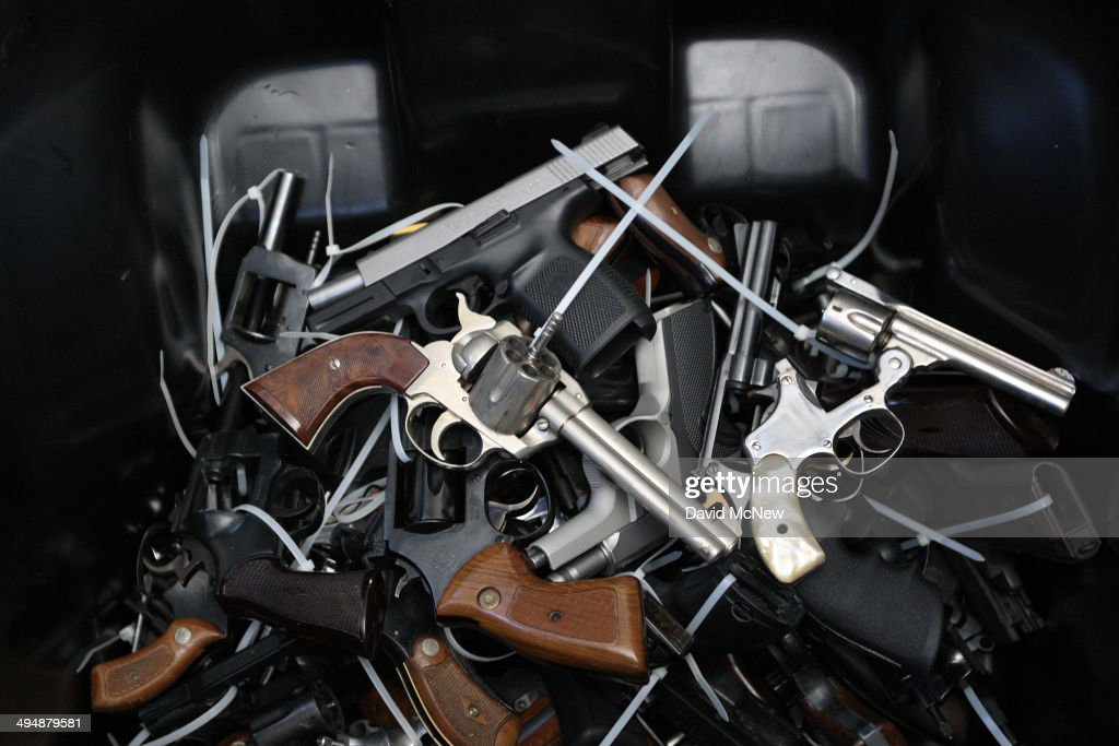 Surrendered handguns are piled in a bin during a gun buyback event that was announced by Los Angeles Mayor Eric Garcetti in the wake of a killing...