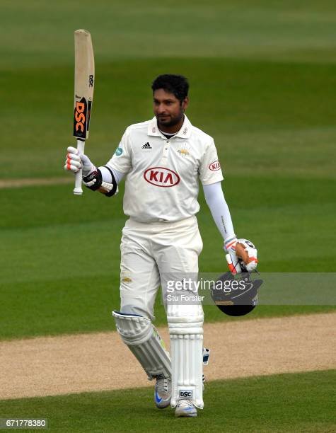 Surrey batsman Kumar Sangakkara raises his bat after reaching his century on day three of the Specsavers County Championship Division One between...