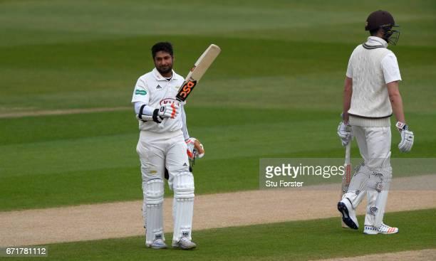 Surrey batsman Kumar Sangakkara raises his bat after reaching his century on day three of the Specsavers County Championship Division One between...