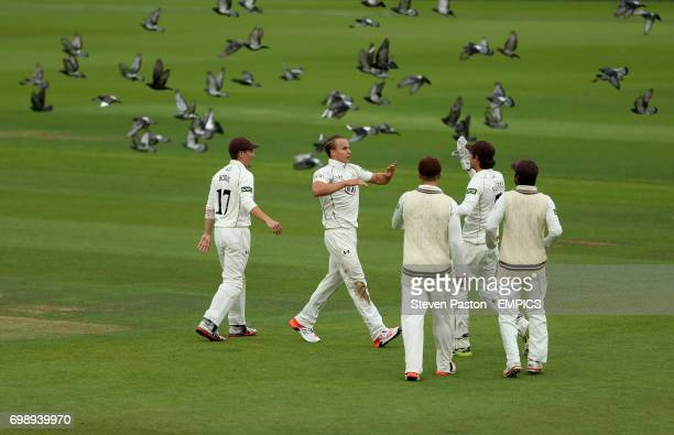 Surrey bowler Tom Curran celebrates with teammates of the wicket of Kent's Sam Northeast
