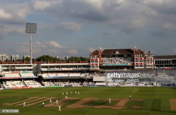 Surrey's bowler Timothy Linley watches on as Middlesex's James Harris knocks the ball away in the late afternoon sunlight