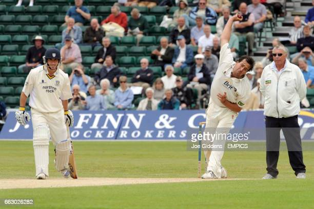 Surrey's James Ormond bowls against Durham as umpire Michael Harris looks on