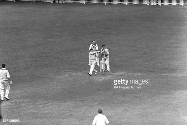 Surrey's Jim Laker slogs a boundary watched by MCC wicketkeeper Godfrey Evans