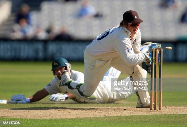 Surrey's Lee Hodgson attempts a run out on Nottinghamshire's Charlie Shreck