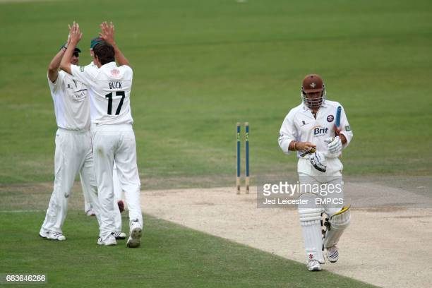 Surrey's Mark Ramprakash walks off the pitch looking dejected as Leicestershire's Nathan Buck celebrates taking his wicket for 274 runs
