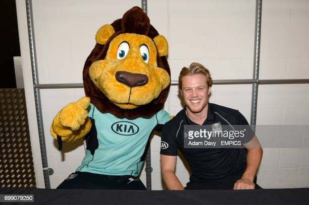 Surrey's Matt Dunn and club mascot Caesar the Lion pose for a photo during the Family Day