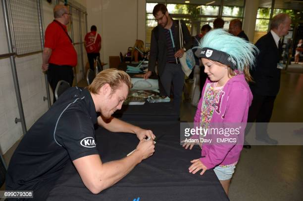 Surrey's Matt Dunn signs autographs for fans during the Family Day