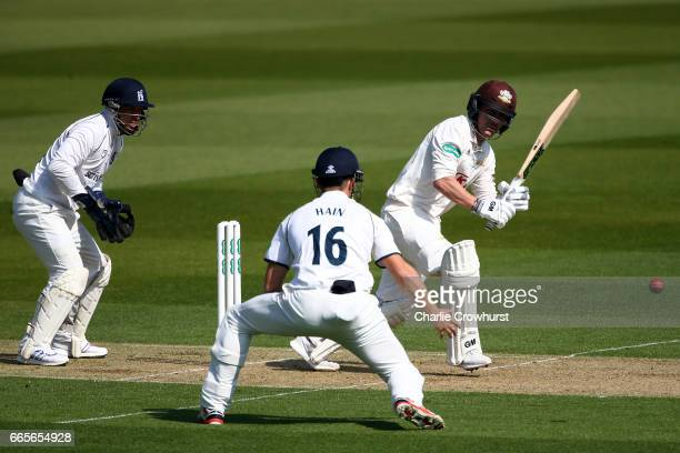 Surrey's Rory Burns hits out while Warwickshire's wicket keeper Tim Ambrose and silly point Sam Hain watch on during the Specsavers County...