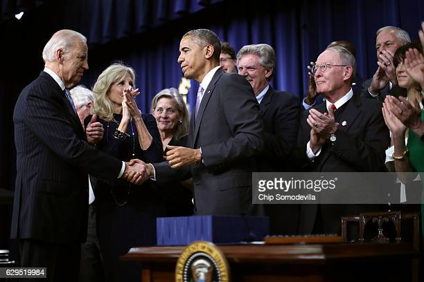 Surrounded by advocates and lawmakers US President Barack Obama shakes hands with Vice President Joe Biden after signing the 21st Century Cures Act...