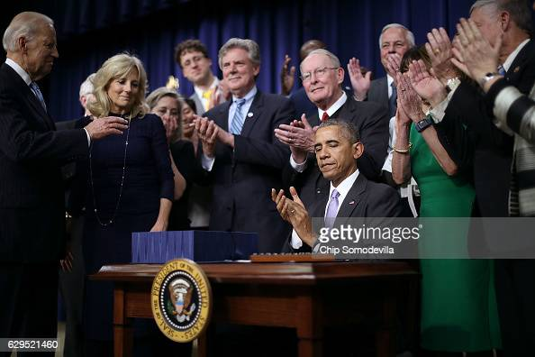 Surrounded by advocates and lawmakers US President Barack Obama applauds after signing the 21st Century Cures Act into law at the Eisenhower...