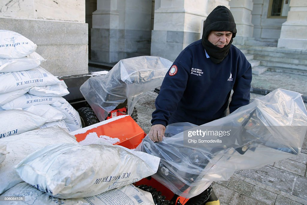 Surrounded by bags of icemelting salt stone mason Medaro Romero covers gas powered snow sweepers in plastic bags in preparation for a coming winter...
