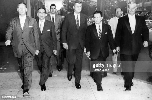 Surrounded by Boston and State Police officers Senator John F Kennedy strides along Arlington Street on way to a breakfast at the Statler Hilton...