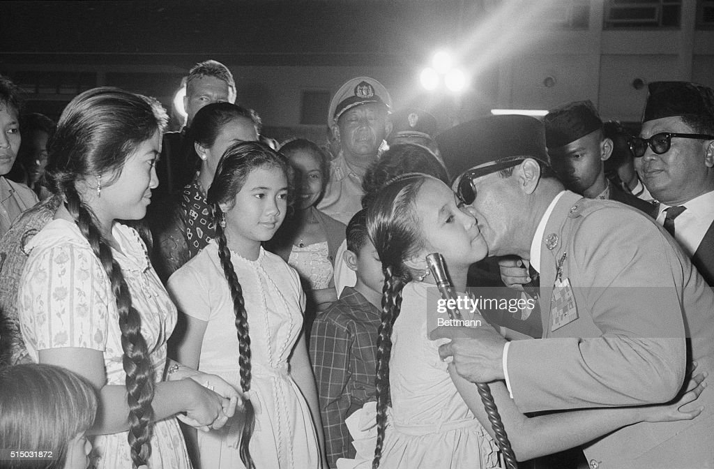 Surrounded by citizens of Jakarta, President <a gi-track='captionPersonalityLinkClicked' href=/galleries/search?phrase=Sukarno&family=editorial&specificpeople=209275 ng-click='$event.stopPropagation()'>Sukarno</a> kisses his youngest daughter, Sukmawati, goodbye while his other daughters, Rachmawati (center) and Megawati (left), wait their turn. The Indonesian President was leaving for a three-week vacation in Tokyo.