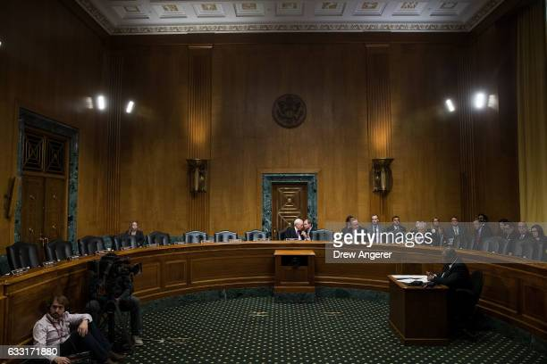 Surrounded by empty seats Senator and committee chairman Orrin Hatch confers with an aide during a meeting of the Senate Finance Committee to vote on...