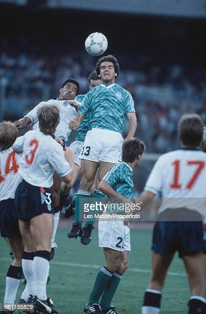 Surrounded by England players West German footballer KarlHeinz Riedle leaps to head the ball in the 1990 FIFA World Cup semifinal game between...