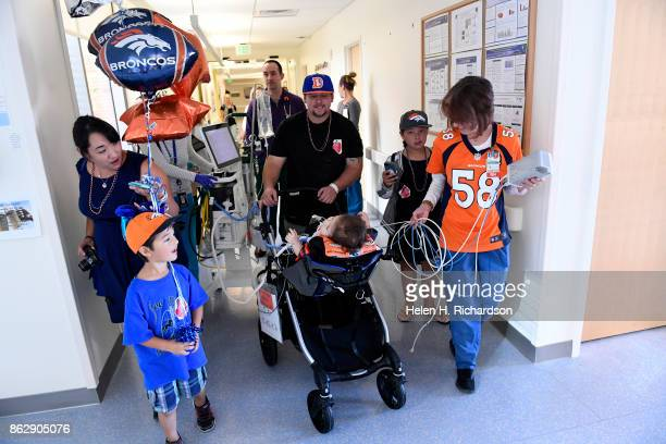 AURORA CO OCTOBER 18 Surrounded by family Casey Christensen middle pushes a chair with his son Ryker down the hospital corridor towards an outdoor...