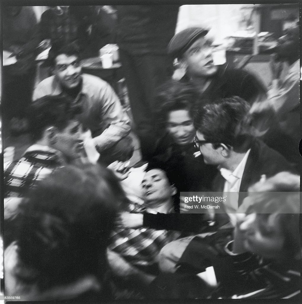 Surrounded by groupies, American author Jack Kerouac (1922 - 1969) (center) lies down during a break in poetry reading at the Artist's Studio (48 East 3rd Street), New York, New York, February 15, 1959.