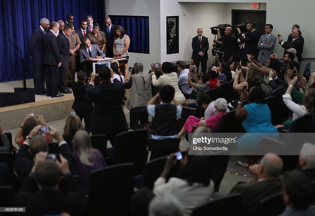 Surrounded by invited guests, including Labor Secretary Tom Perez, U.S. President <a gi-track='captionPersonalityLinkClicked' href=/galleries/search?phrase=Barack+Obama&family=editorial&specificpeople=203260 ng-click='$event.stopPropagation()'>Barack Obama</a> signs an executive order that requires government contractors to make public previous labor law violations and give their workers more rights to address disputes in the Eisenhower Executive Office Building July 31, 2014 in Washington, DC. Obama signed the labor order a day after House Republicans voted to go forward with a lawsuit against the president in an attempt to stop him from acting on his own with executive orders.