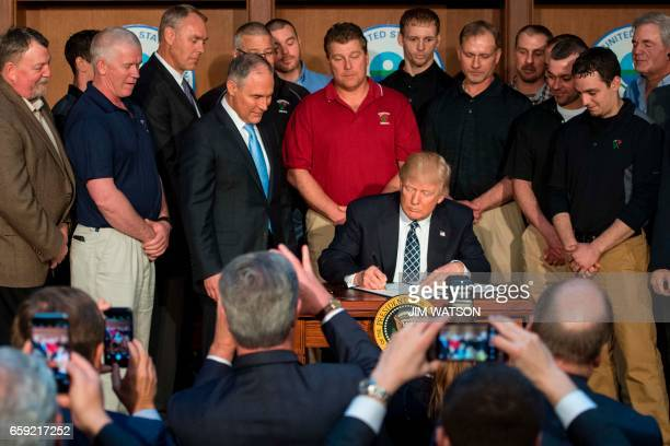 TOPSHOT Surrounded by miners from Rosebud Mining US President Donald Trump signs he Energy Independence Executive Order at the Environmental...