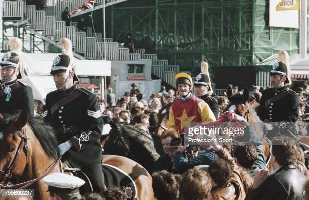 Surrounded by mounted police officers British jockey Richard Dunwoody and Irish bred mount Miinnehoma are led in after finishing in first place to...