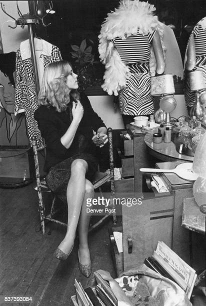Surrounded by New Wave fashion Leslie Flice primps at dressing table wearing a black wool jacket over glittery blue top and skirt pointytoe glitter...