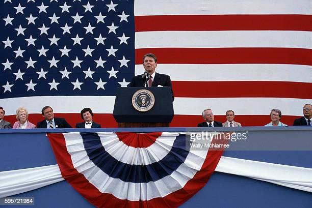 Surrounded by patriotic bunting and a large American flag President Ronald Reagan gives a speech in New York New York Senator Alfonse D'Amato listens...