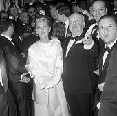Surrounded by photographers film director Alfred Hitchcock escorts Tippi Hedren the star of his new film The Birds to a screening of the film at the...