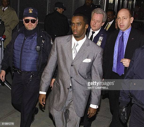 Surrounded by police officers rapper Sean 'Puffy' Combs leaves State Supreme Court in New York City 15 March after a jury failed to reach a verdict...