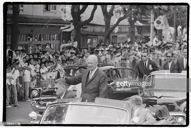 Surrounded by Secret Service agents President Eisenhower rides in his motorcade to address the South Korean National Assembly waving to the passerby...