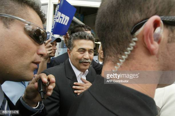 Surrounded by security Labour party leader Amir Peretz gestures during his election campaign tour of Jerusalem 21 March 2006 Israel's general...