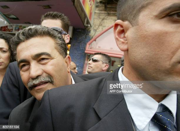 Surrounded by security Labour party leader Amir Peretz leans out to listen to an Israeli citizen during his election campaign tour of Jerusalem 21...