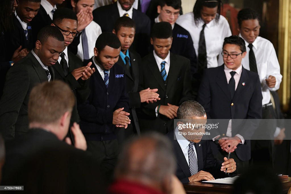 Surrounded by students from the ChicagoÕs Youth Guidance program Becoming a Man (BAM), U.S. President <a gi-track='captionPersonalityLinkClicked' href=/galleries/search?phrase=Barack+Obama&family=editorial&specificpeople=203260 ng-click='$event.stopPropagation()'>Barack Obama</a> signs an executive memorandum related to his 'My Brother's Keeper' initiative in the East Room at the White House February 27, 2014 in Washington, DC. As part of his 'Year of Action,' Obama announced a $200 million commitment from nine foundations to bolster the education and employment of young men and boys of color.