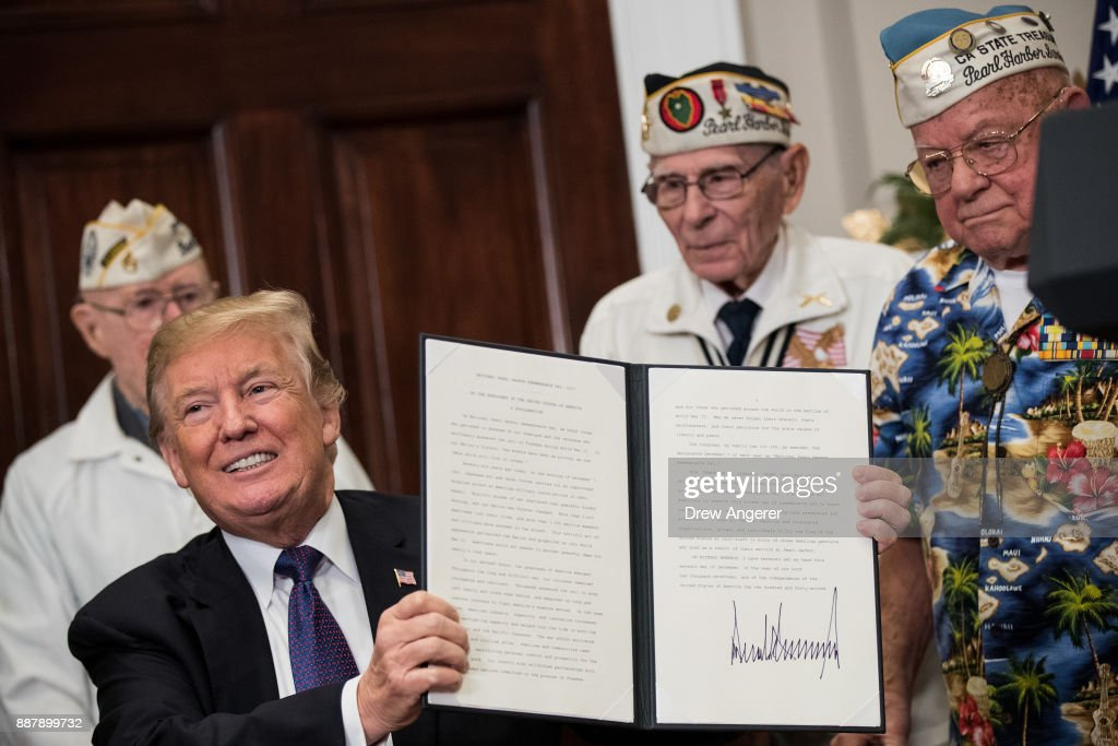 Surrounded by survivors of the 1941 attack on Pearl Harbor, President Donald Trump signs a proclamation for National Pearl Harbor Remembrance Day, in the Roosevelt Room of the White House, December 7, 2017 in Washington, DC. Thursday is the 76th anniversary of the attacks against the Hawaii naval base.