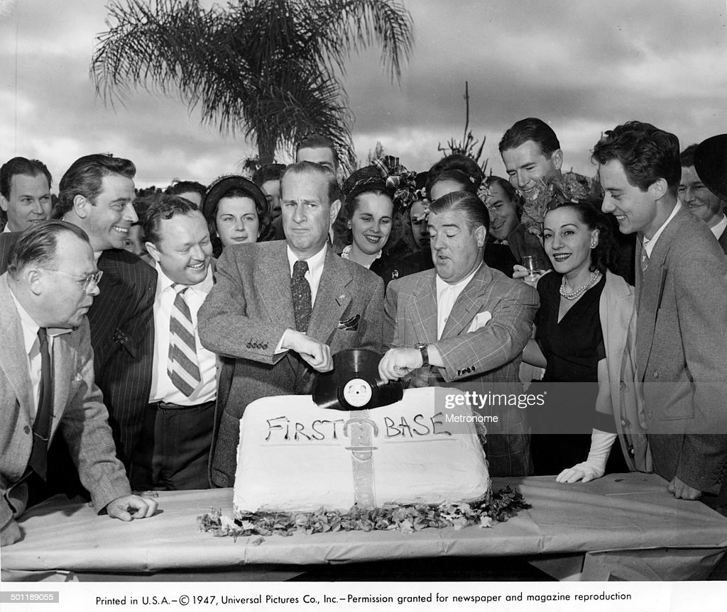 Surrounded by unidentified others, American comedians <a gi-track='captionPersonalityLinkClicked' href=/galleries/search?phrase=Bud+Abbott&family=editorial&specificpeople=228402 ng-click='$event.stopPropagation()'>Bud Abbott</a> (1895 - 1974) (center left) & <a gi-track='captionPersonalityLinkClicked' href=/galleries/search?phrase=Lou+Costello&family=editorial&specificpeople=123845 ng-click='$event.stopPropagation()'>Lou Costello</a> (1906 - 1959) (and center right) 'pull' a vinyl record of their 'Who's On First?' comedu routine from a cake labelled 'First Base,' 1947.
