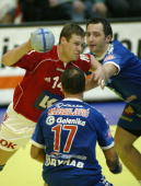 Danish Michael Knudsen is sandwiched by Serbian Alem Toskic and Zikica Milosavljevic in the local sports hall of Sursee 29 January 2006 during a...