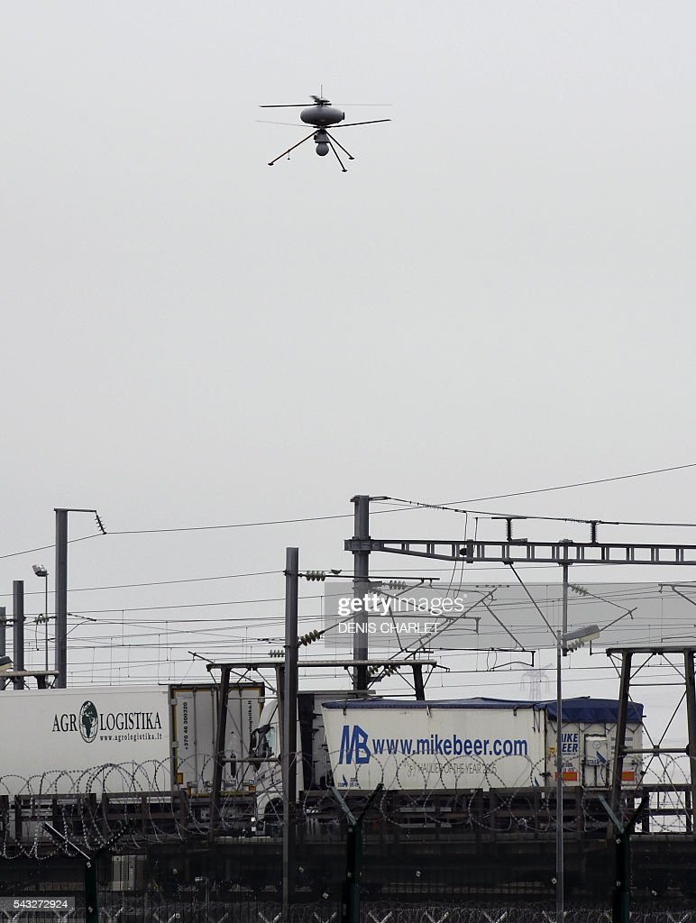 A surveillance drone (or UAV for unmanned aerial vehicle) fly over the Channel Tunnel on June 27, 2016 in Coquelles, northern France. The Eurotunnel Group acquired two military drones with a thermal infra-red camera for monitoring the 650 hectares area against potential instrusions of migrants who try to reach Britain by the Channel Tunnel. / AFP / DENIS