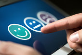 Survey, poll or questionnaire for user experience or customer satisfaction research. Quality control and feedback concept. Man choosing his opinion with smiley faces on touch screen.