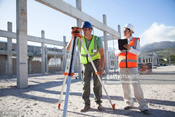 Surveyor and architect working at construction site