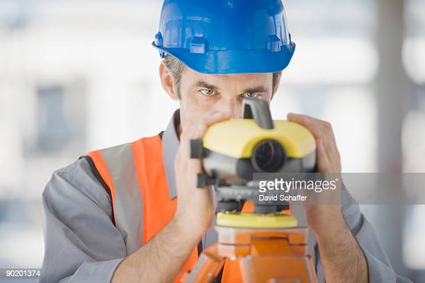 Surveyor in hard-hat using surveying equipment