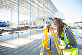 Surveyor leaning forward to look through level on construction site